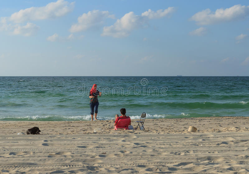 Young arab couple relaxing on the beach on a sunny summer day stock photos