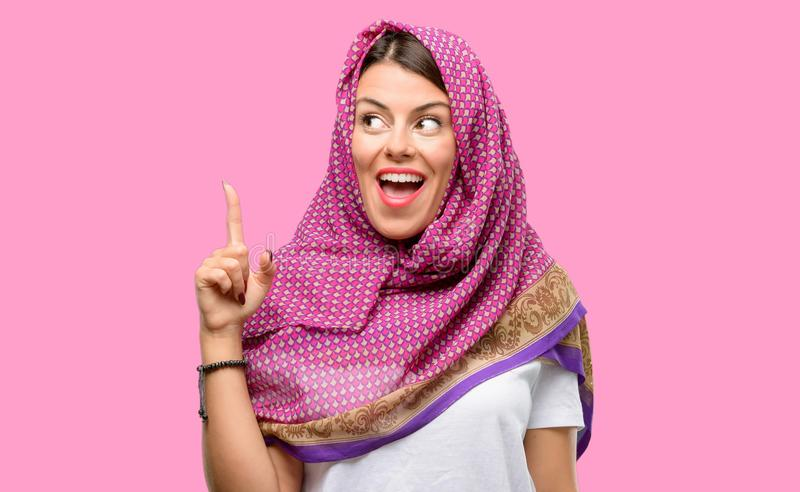 Young arab woman. Wearing hijab pointing away side with finger stock photos