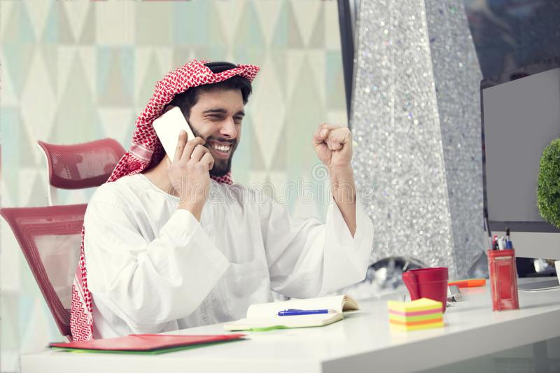 Young Arabian business man talking on mobile phone and working finance about cost with laptop computer. Young Arabian business man talking on mobile phone and stock photography