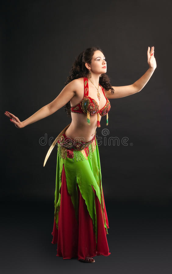 Young Arabian dancer with saber. On hip - green and red stock images