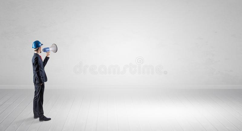 Architect standing in an empty space and holding a plan royalty free stock images