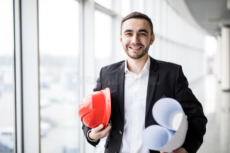 Young architect holding print and hamlet in office , engineering and contractor concept stock images