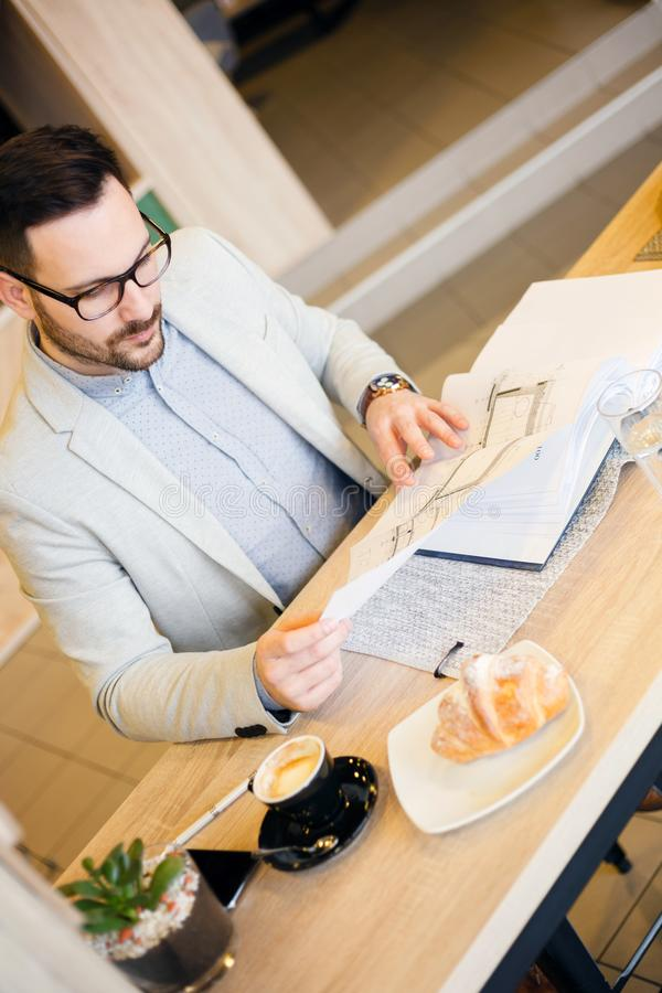 Young architect or engineer looking over building plans while working in a modern cafe royalty free stock photography