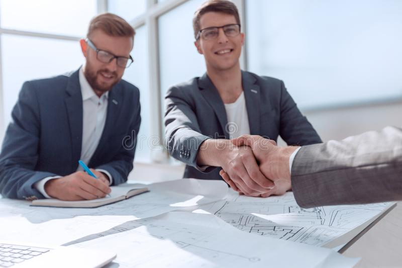 Young architect shaking hands with the customer sitting at his Desk stock photography