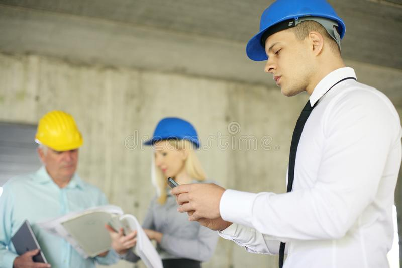 Young architect using mobile phone. royalty free stock photos