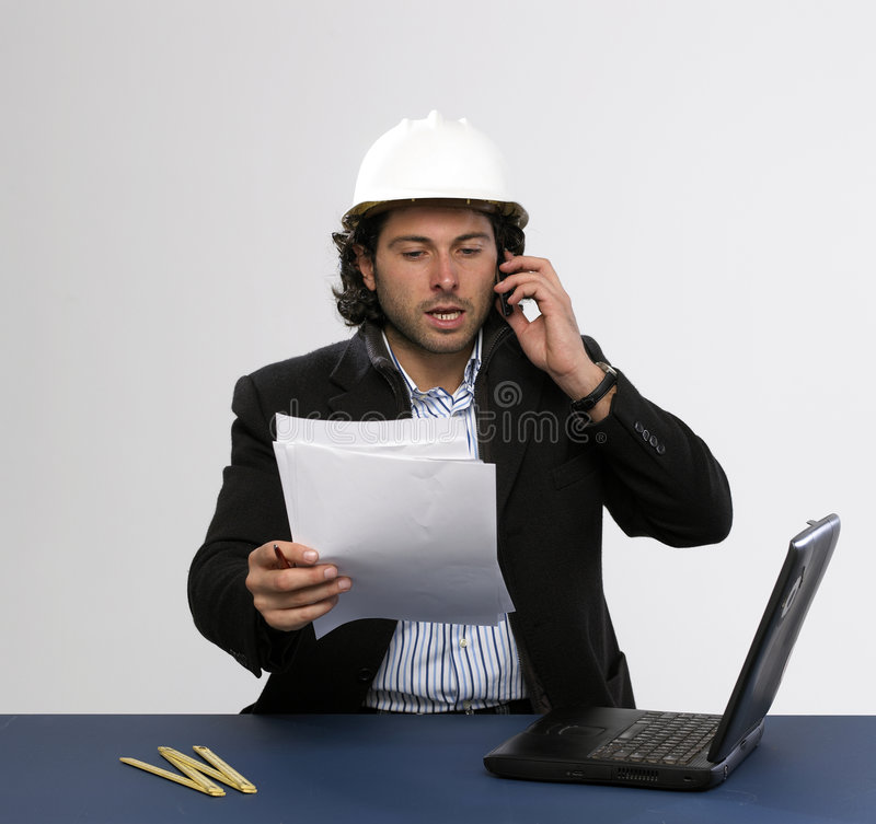Young architect at work. Is talking on mobilphone stock photography