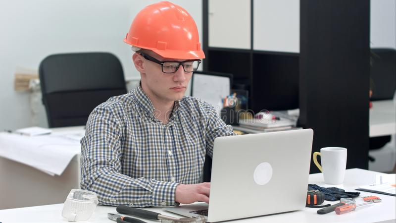 Young architect working on the laptop in office stock images