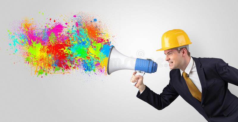 Young architect yelling with megaphone and colorful splash concept royalty free stock images