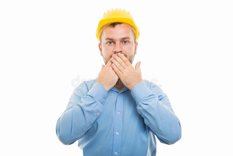Young architect with yellow helmet covering mouth stock image