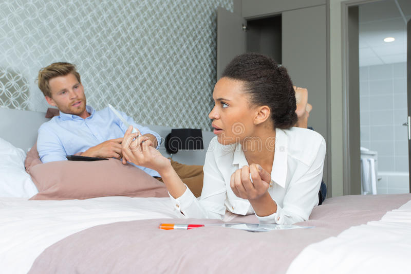 Young arguing couple in bed stock photography