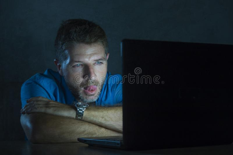 Young aroused and excited sex addict man watching mobile online in laptop computer light night at home in. Young aroused and excited sex addict man watching stock photo