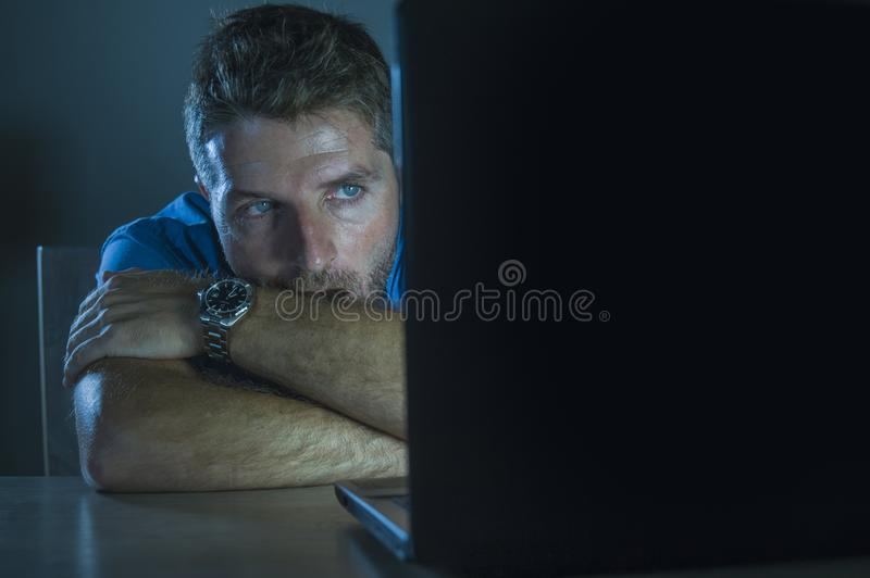Young aroused and excited sex addict man watching mobile online in laptop computer light night at home in. Young aroused and excited sex addict man watching royalty free stock photos