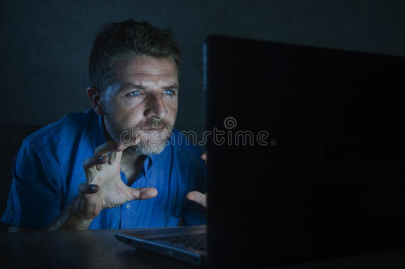 Young aroused and excited sex addict man watching mobile online in laptop computer light night at home in. Young aroused and excited sex addict man watching stock image