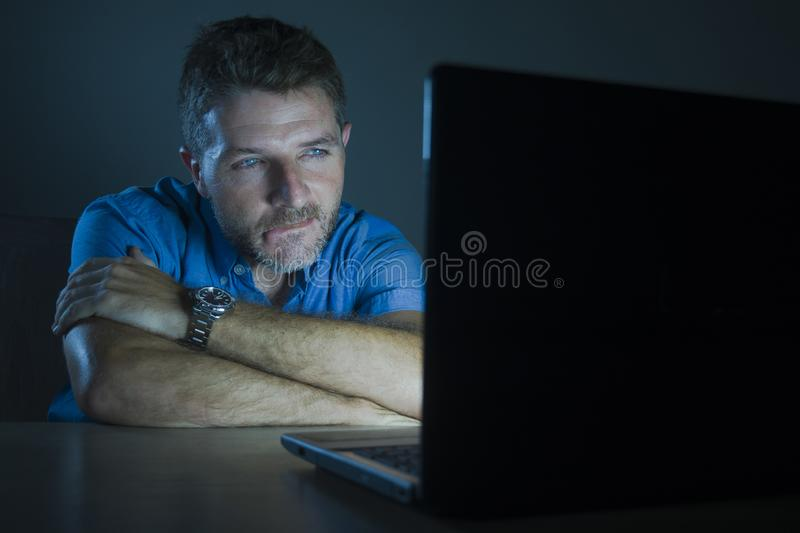 Young aroused and excited sex addict man watching mobile online in laptop computer light night at home in. Young aroused and excited sex addict man watching stock images