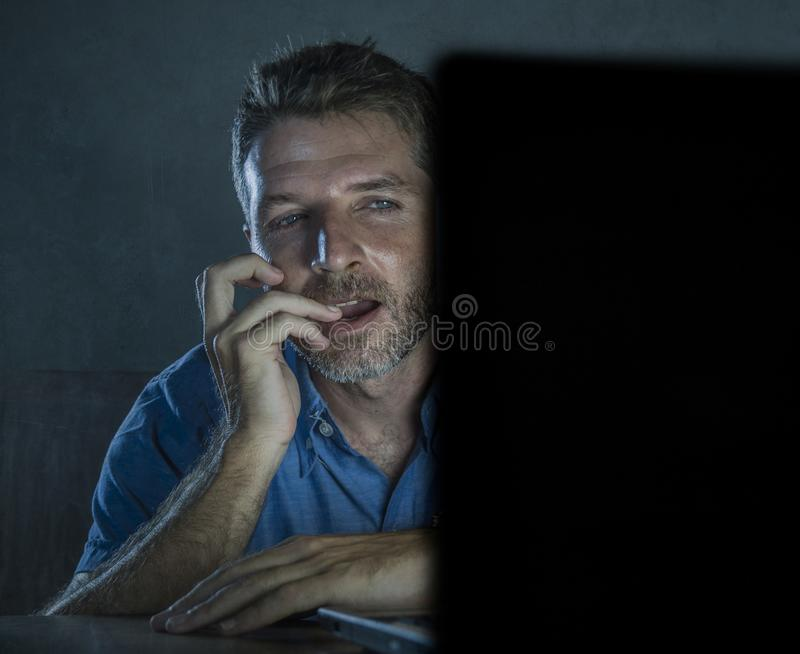Young aroused and excited sex addict man watching mobile online in laptop computer light night at home in. Young aroused and excited sex addict man watching royalty free stock images