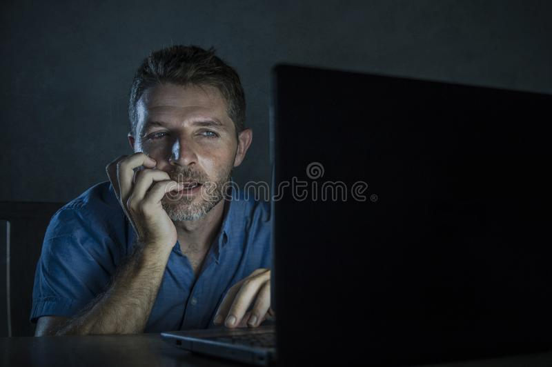 Young aroused and excited sex addict man watching mobile online in laptop computer light night at home in. Young aroused and excited sex addict man watching royalty free stock photo