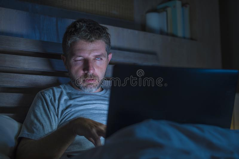 Tired and stressed workaholic man working late night exhausted on bed busy with laptop computer feeling sleepy suffering business. Young aroused man alone in bed royalty free stock image