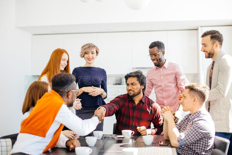Young arrogant intern Hindoo employee is shaking hands with co-workers. While drinking coffee. closeup portrait stock photography