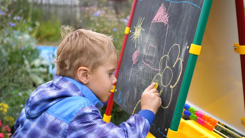Young artist draws on the Board. A boy in the open air among the flowers and greenery draws children`s pictures with stock photos