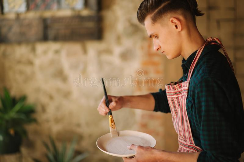 Young artist making ornament on ceramic plate. Handsome young man working at his workshop royalty free stock photos