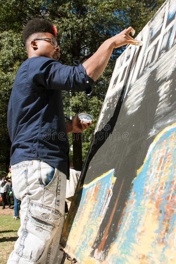 Young Artist Paints With His Fingers At Atlanta Arts Festival. Atlanta, GA, USA - October 17, 2015: A young African-American artist paints with his fingers in royalty free stock images
