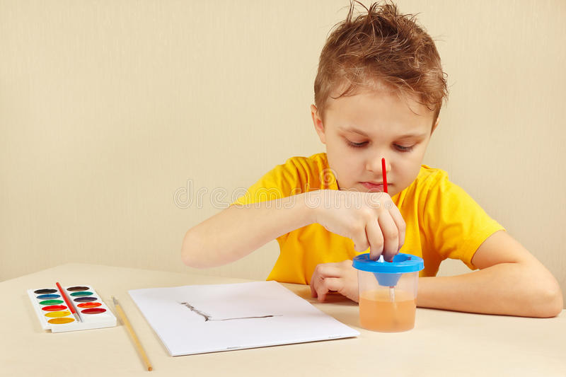 Young artist in yellow shirt painting colors. Young artist in a yellow shirt painting colors stock photos