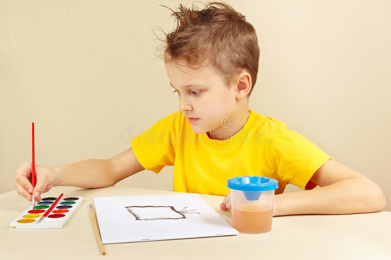 Young artist in yellow shirt painting with watercolors. Young artist in a yellow shirt painting with watercolors royalty free stock photos