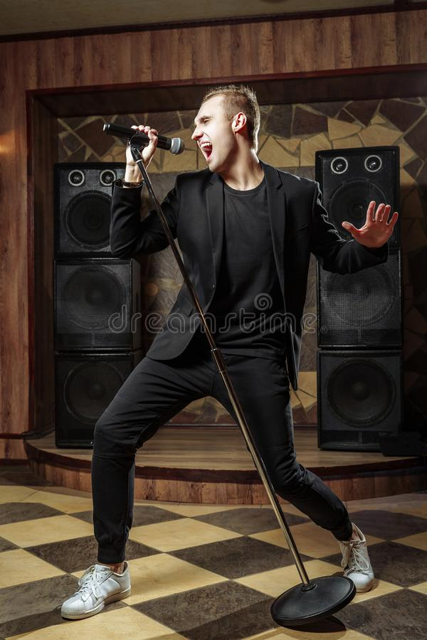 Young artistic man singing with microphone.  stock photos