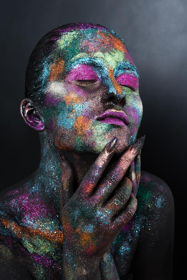 Young artistic woman in black paint and colourful powder. Glowing dark makeup. Creative body art on the theme of space stock photos
