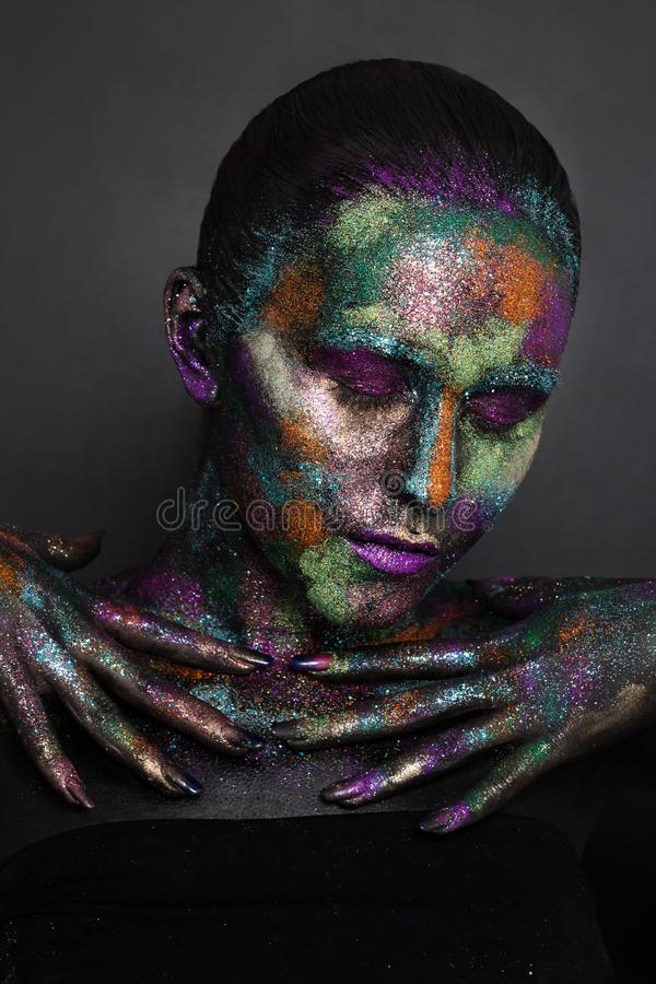 Young artistic woman in black paint and colourful powder. Glowing dark makeup. Creative body art on the theme of space stock photography