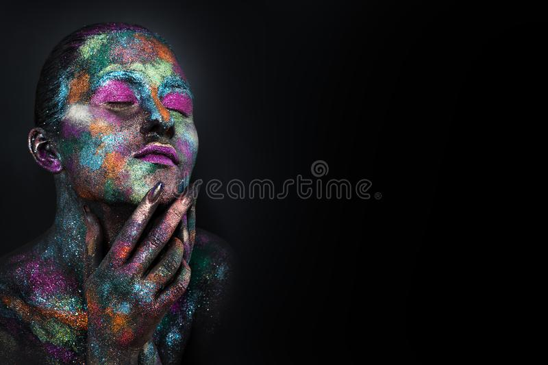 Young artistic woman in black paint and colourful powder. Glowing dark makeup. Creative body art on the theme of space royalty free stock photos