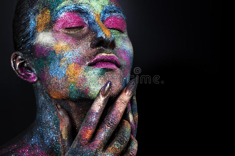 Young artistic woman in black paint and colourful powder. Glowing dark makeup. Creative body art on the theme of space royalty free stock photo