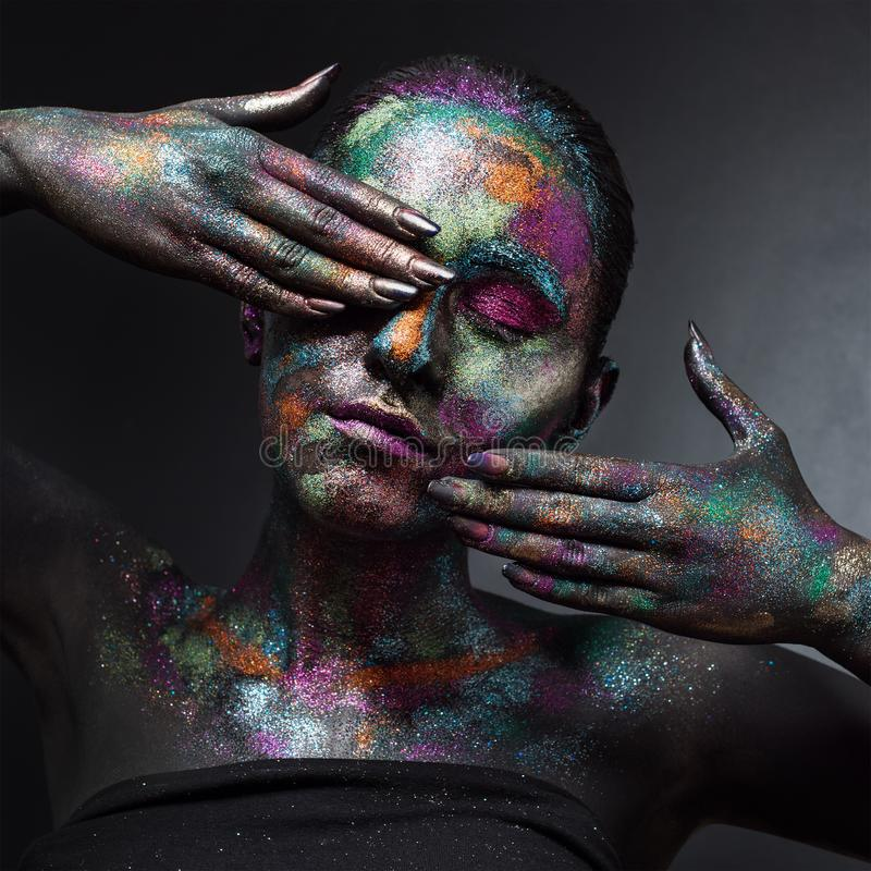 Young artistic woman in black paint and colourful powder. Glowing dark makeup. Creative body art on the theme of space stock image