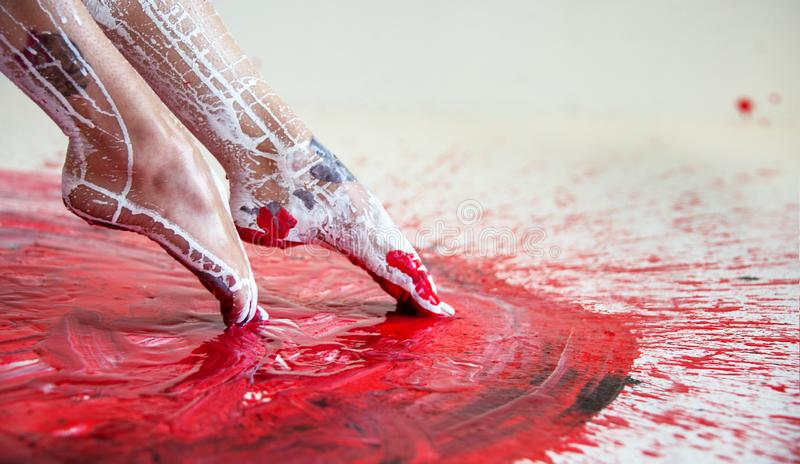 Young artistically abstract painted woman ballerina with black red white, paint, pokes her feet in red paint, Creative body art stock photo