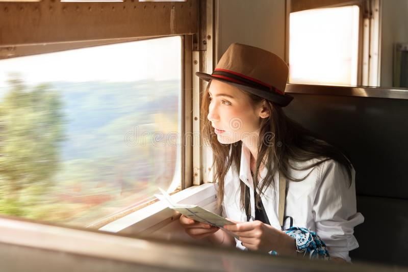 Young Asia backpacker woman travels her journey by train, travel. Ing to countryside in classic train sitting and looking out of a train window,Thailand royalty free stock photography