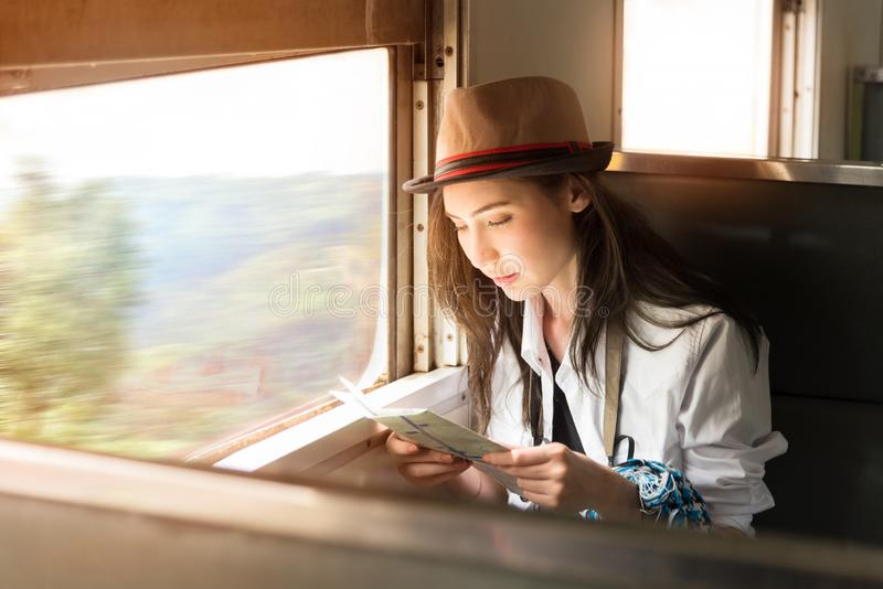 Young Asia backpacker woman travels by train. Young Asia backpacker woman travels her journey by train, traveling to countryside in classic train sitting and stock image