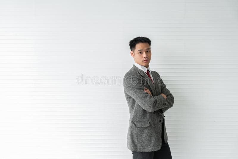 Young Asia businessman stands crossed its back with confidence against a gray wooden backdrop stock images