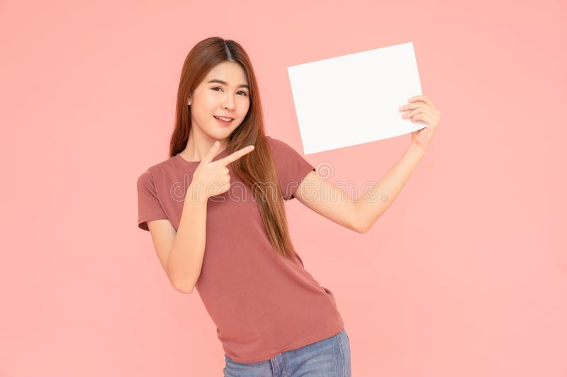 Young asia smiling woman holding advertising sign board and pointing finger. Isolated portrait on pink background with copy space stock photography