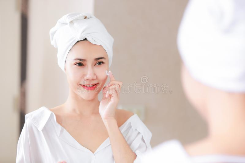 Young asia woman applying foundation or moisturizer on her face. In front of mirror stock photo