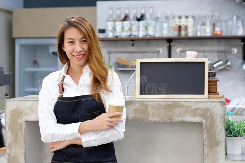 Young asia woman barista holding a diaposable coffee cup with sm. Iling face at cafe counter background, small business owner, food and drink industry concept stock image