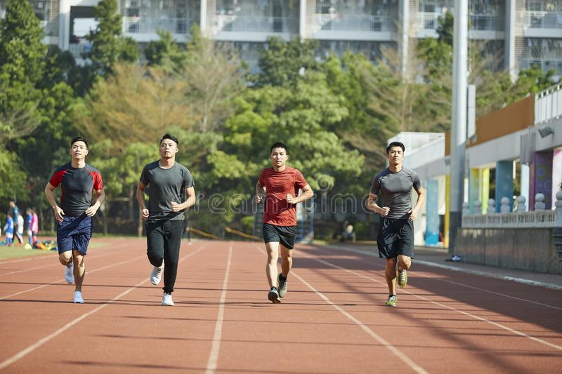 Young asian athletes running on track royalty free stock image