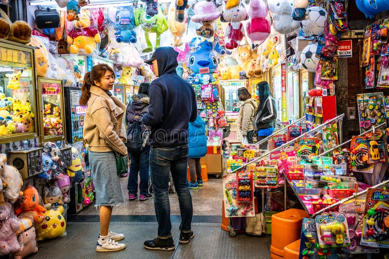 Young Asian adult couple on the porch of a colorful toys and games shop in Taipei Taiwan stock image