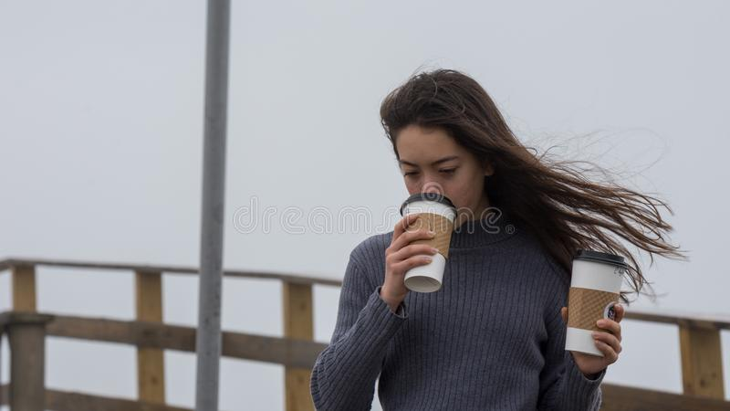 Young Asian-American at North Carolina Beach in winter with cups in hand stock image
