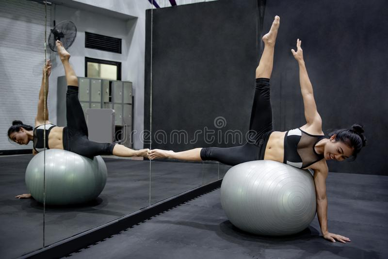 Asian athlete woman doing exercise with ball stock images