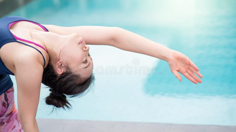 Young Asian woman doing yoga exercise near swimming pool royalty free stock photo