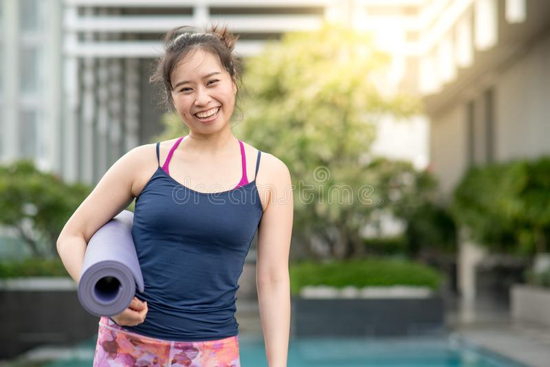 Young Asian woman holding yoga mat at swimming pool royalty free stock photo