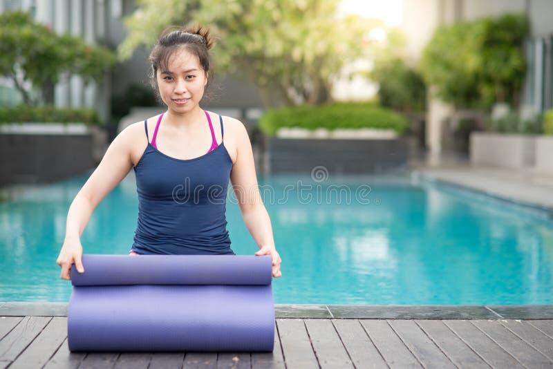 Young Asian woman rolling yoga mat near swimming pool stock image