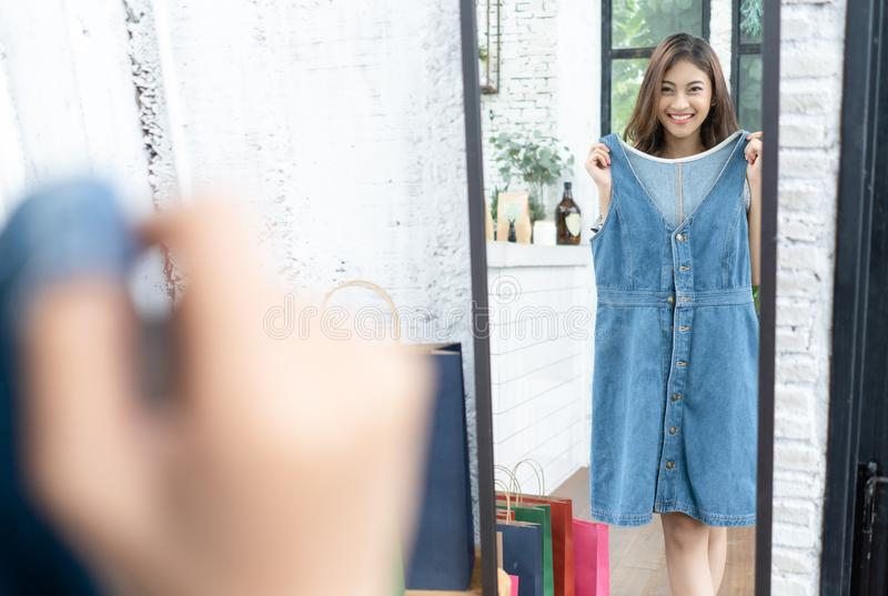 Young Asian attractive woman trying on a blue jean dress in a fashion store, looking at her reflection in a mirror. Shopping, royalty free stock photography