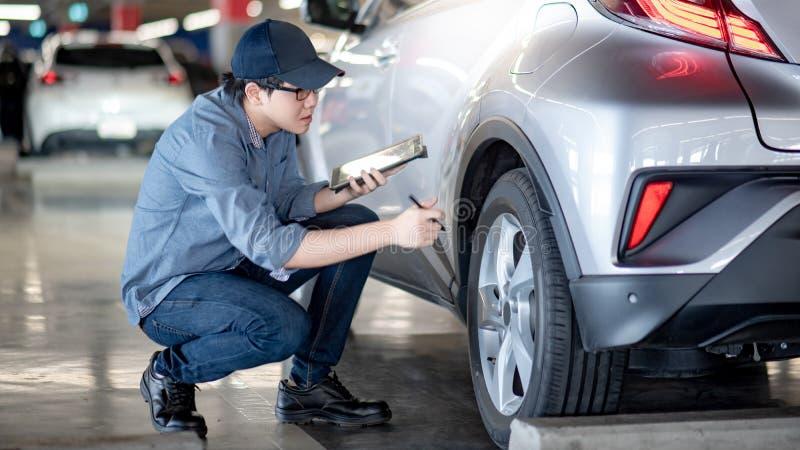 Asian auto mechanic checking the car using tablet. Young Asian auto mechanic holding digital tablet checking car wheel in auto service garage. Mechanical stock photos