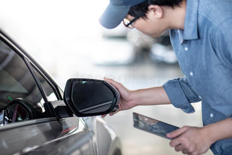 Asian auto mechanic checking car wing mirror. Young Asian auto mechanic holding digital tablet checking car wing mirror. Mechanical maintenance engineer working royalty free stock image